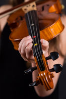 Close up of professional violin in hands of little girl playing it on black background