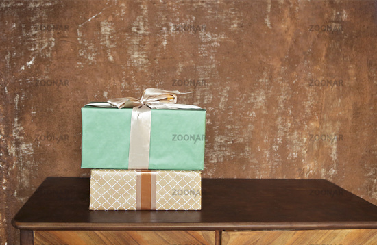 Stack of handcraft gift boxes on wooden board with a natural textured background
