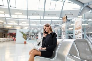 Junge Geschäftsfrau mit Smartphone im Flughafen