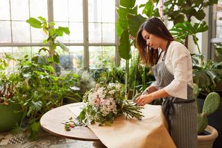 Floristin beim Blumenstrauß binden für den Versand