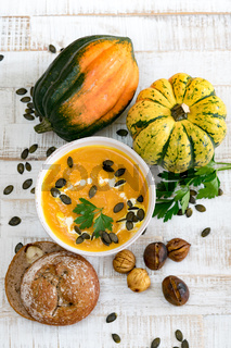 organic pumpkin soup in a white bowl framed by chestnuts pumpkins parsley and chestnut bread