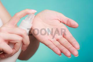 Woman putting white cream on hand
