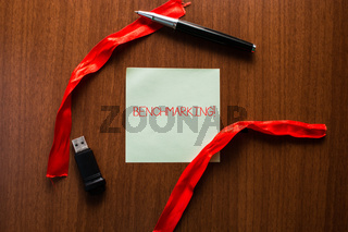 Text sign showing Benchmarking. Conceptual photo evaluate something by comparison with standard or scores USB memory lying wooden table square blank note stripes ribbon up down pen.