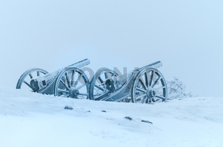 Old metal cannons covered with snow.