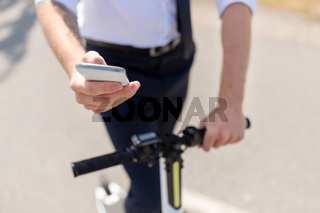 businessman with smartphone and electric scooter