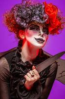 A closeup of a scarier clown female Holding Knife