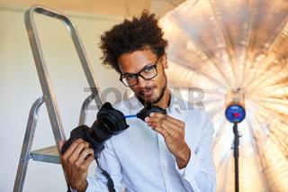 Fotograf reinigt Kamera Objektiv mit dem Blasebalg