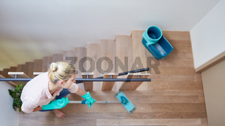 Putzfrau mit Wischmopp beim im Treppenhaus