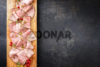 Traditional lunch meat with sliced cold cuts roast beef decorated with red ribes as top view on a cutting board with copy space right