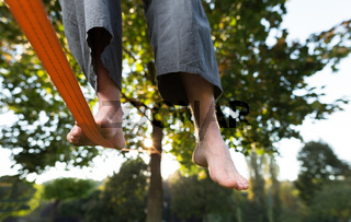 Closeup of mans feet balancing a tightrope or slackline in park environment with one foot above rope.
