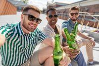 men drinking beer and taking selfie on street