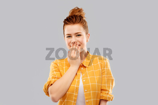 confused red teenage girl covering mouth by hand