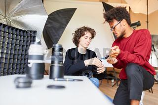 Fotoassistentin hilft Fotograf bei Objektivreinigung