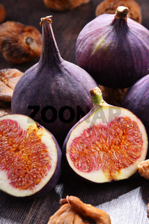 Composition with fresh and dried figs on wooden table.