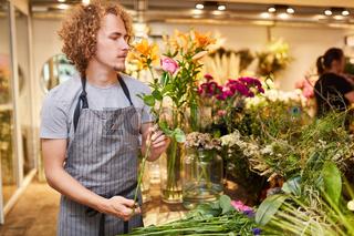 Junger Mann als Florist beim Rosenstrauß binden