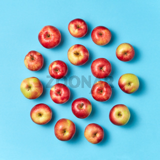 Organic apples round pattern on a blue background.