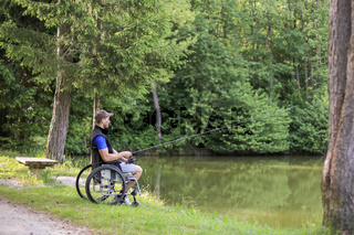 Disabled man on wheelchair fishing in nature
