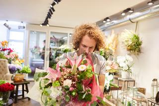 Florist bindet einen Blumenstrauß als Geschenk