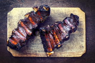 Barbecue chuck beef ribs with hot marinade as top view on a wooden cutting board with copy space - vintage