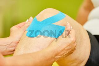 Patient bekommt ein Kinesio Tape ans Kniegelenk