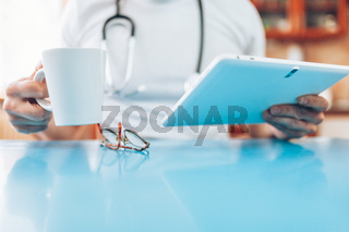 Doctor in his practice working with a digital tablet