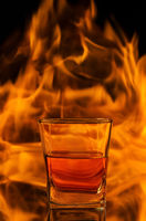 Whiskey in a glass on a background of fire