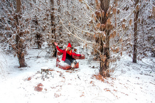 Woman on a couch among the snow covered pine forest in winter