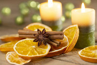 Christmas or advent decoration - candles with orange slices and spices on old wood