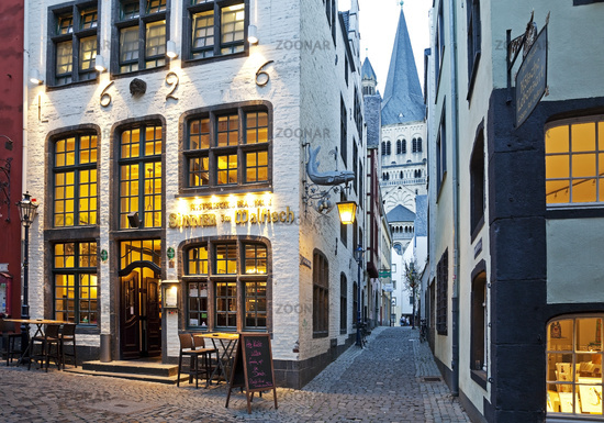 Salzgasse with restaurant, view through narrow lane to Great St. Martin Church, Cologne, Germany