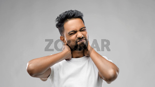 tired indian man suffering from neck pain