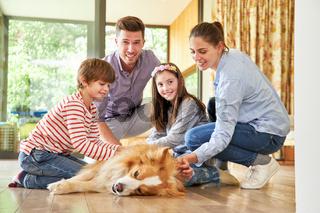 Eltern und glückliche Kinder streicheln Hund