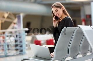 Frau auf Geschäftsreise mit Laptop und Smartphone