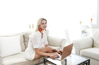 Woman drinking a coffee and using her laptop in the living room