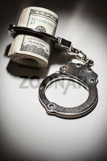 Handcuffs Locked on Roll of One Hundred Dollar Bills Under Spotlight