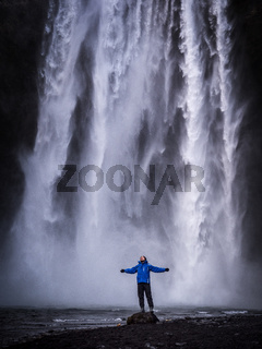 Traveler with outstretched arms near waterfall in Iceland