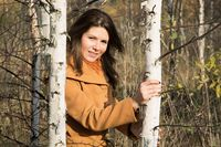girl in autumn day among young trees in the forest