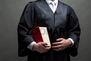 deutscher Rechtsanwalt mit Robe und Buch