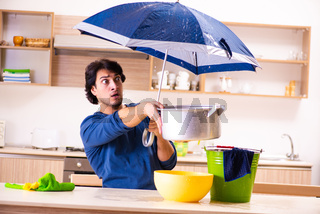 Young man in water leakage from the neighbors concept