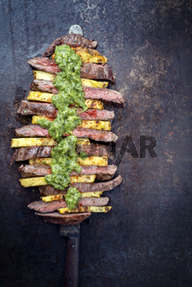 Traditional Barbecue dry aged wagyu flank steak with pineapples and chimichurri sauce as top view on a knife on an old metal sheet with copy space right