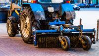 Wheel tractor cleans the sidewalk