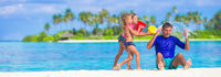 Adorable little girls having fun with dad on white beach