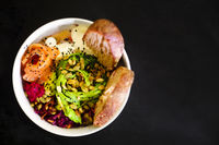 Organic food. Fresh seafood recipe. Fresh salmon poke bowl with rice, egg, bread, fresh red cabbage, avocado, radish sprouts on dark background