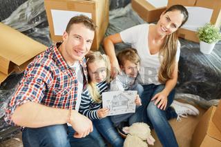 Eltern und Kinder mit Bild vom Eigenheim