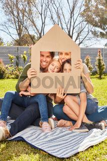 Eltern und zwei Kinder halten ein Modell Haus