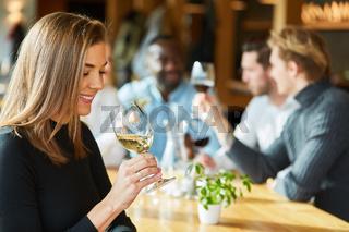 Frau trinkt ein Glas Weißwein im Restaurant