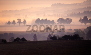 Autumn foggy and misty sunrise landscape