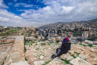 Two People Sitting Together Headscarves Looking Out at Jordan City Landscape Travel Middle East Ruins