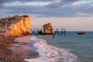 People enjoy themselves at the beach againt the Petra tou Romiou rocks bathed in afternoon light, in Paphos, Cyprus. The beach is considered to be Aphrodite's birthplace in Greek mythology.