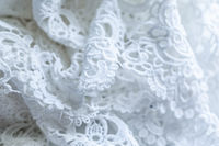 The texture of lace on a white background. Closeup of rippled white fabric. Abstract background of luxurious cloth for a wedding dress