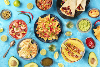 Mexican food, many dishes of the cuisine of Mexico, flat lay, shot from the top on a vibrant blue background. Nachos, tequila, guacamole etc